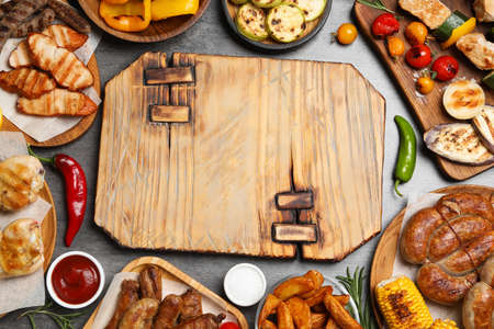 Frame of barbecued meat and vegetables on grey table, flat lay. Space for text Фото со стока - 129830208