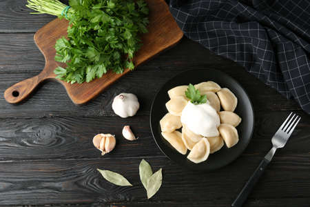 Delicious cooked dumplings with sour cream on dark wooden table, flat lay Фото со стока