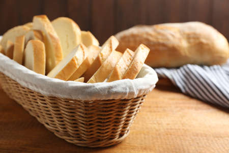 Slices of tasty fresh bread in wicker basket on wooden table, closeup 스톡 콘텐츠