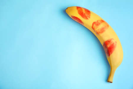 Top view of fresh banana with red lipstick marks on blue background, space for text. Фото со стока - 129904145