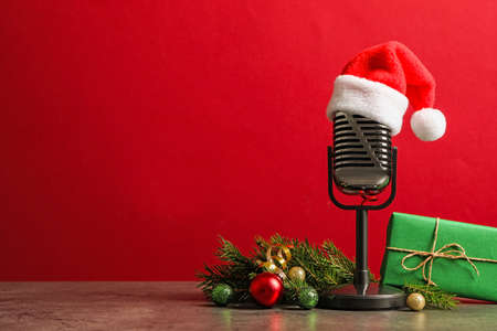 Microphone with Santa hat and decorations on grey table against red background, space for text. Christmas music Stock Photo