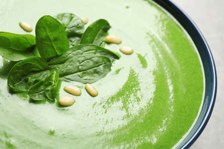 Bowl of healthy green soup with fresh spinach on grey table, closeup view