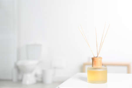 Reed air freshener with essential oils on table in bathroom. Space for text Stock Photo