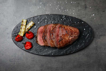 Board with slices of grilled meat on grey table, top view