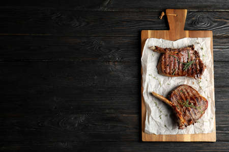 Board with grilled meat on wooden table, top view. Space for text