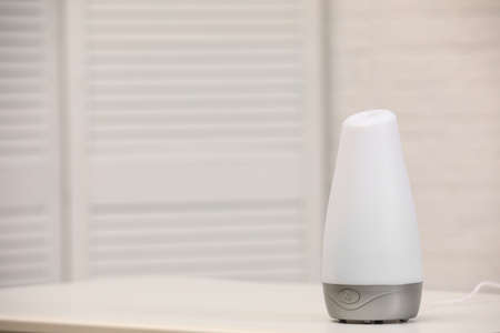 Modern essential oil diffuser on table indoors. Space for text Stock Photo