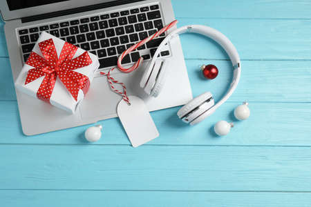 Flat lay composition with headphones on blue wooden background. Christmas music Stock Photo