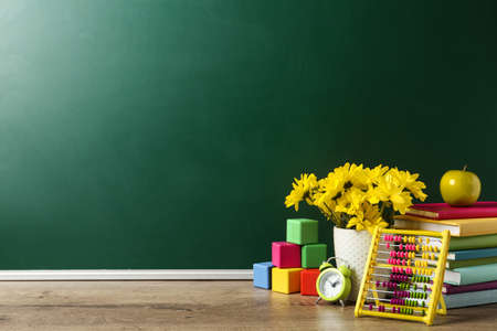 Vase of flowers, books and toys on wooden table near green chalkboard, space for text. Teacher's day