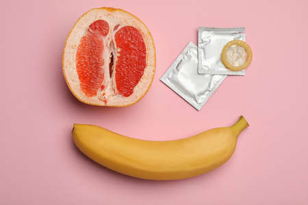 Condoms with banana and cut grapefruit on pink background, flat lay. Safe sex Stock Photo