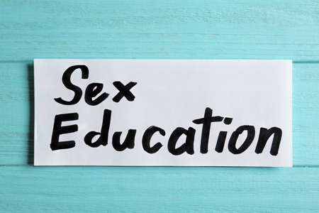 Piece of paper with phrase SEX EDUCATION on light blue wooden background, top view