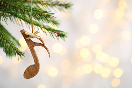 Fir tree branch with wooden note against blurred lights, space for text. Christmas music Stock Photo