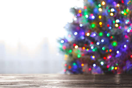 Blurred view of beautiful Christmas tree with colorful lights near window indoors, focus on wooden table. Space for text Stok Fotoğraf