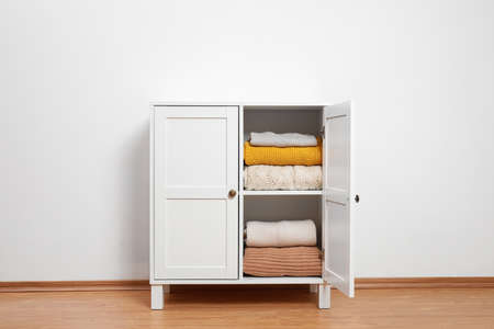 Wooden cabinet with clothes near white wall. Stylish furniture for wardrobe room 스톡 콘텐츠