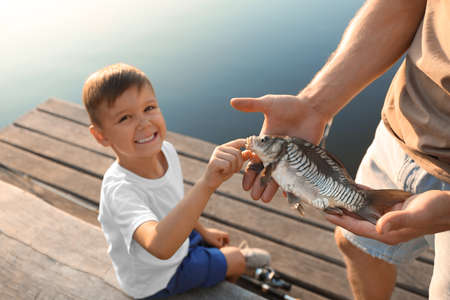 Dad and son holding caught fish at lake Stock fotó