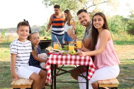 Happy families with little children having picnic in park
