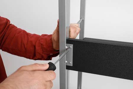 Man fixing shelving unit near white wall, closeup view 写真素材