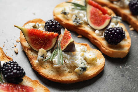 Bruschettas with cheese, figs and blackberries on grey table, closeup Foto de archivo