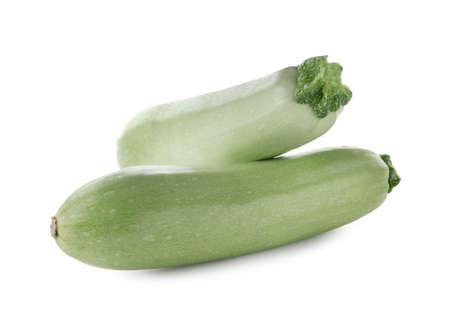 Fresh ripe zucchini squashes on white background
