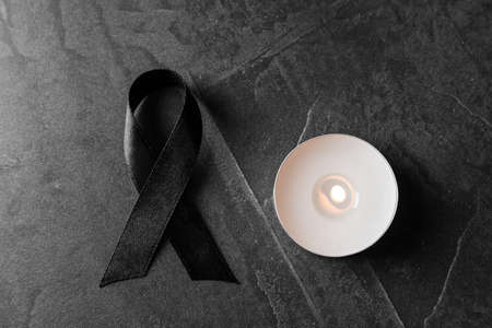 Black ribbon and burning candle on dark grey stone surface, top view. Funeral symbols Stock Photo