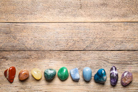 Flat lay composition with different gemstones on wooden table, space for text