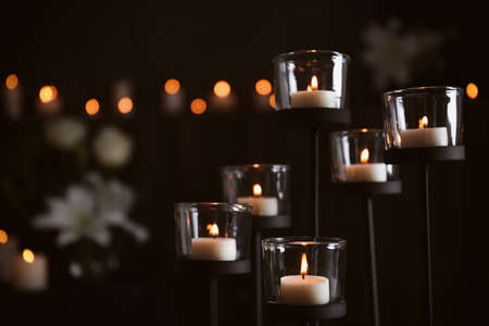 Burning candles on blurred background, space for text. Funeral symbol Stock Photo