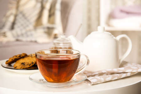 Cup of hot tea on white table indoors. Winter drink