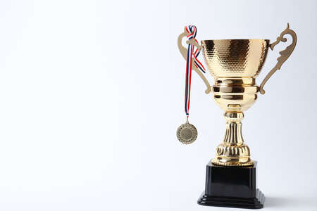 Shiny golden trophy cup and medal on white background