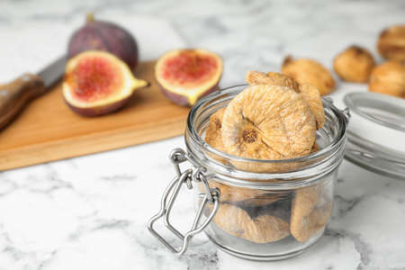 Glass jar of tasty dried figs on marble table. Space for text Banco de Imagens