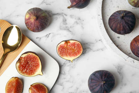 Tasty ripe figs on marble table, flat lay