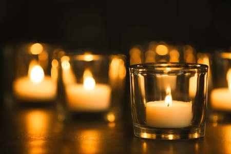 Brennende Kerzen auf dem Tisch in der Dunkelheit. Begräbnissymbol