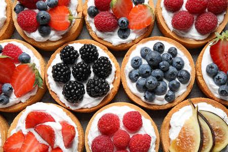 Many different berry tarts on table, top view. Delicious pastries Stock Photo