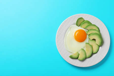 Plate of fried egg and avocado on light blue background, top view with space for text. Healthy breakfast
