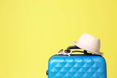 Stylish blue suitcase with hat and sunglasses on yellow background. Space for text Stock fotó