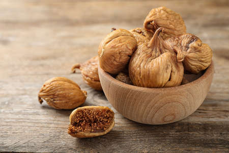Bowl and tasty dried figs on wooden table. Space for text Zdjęcie Seryjne