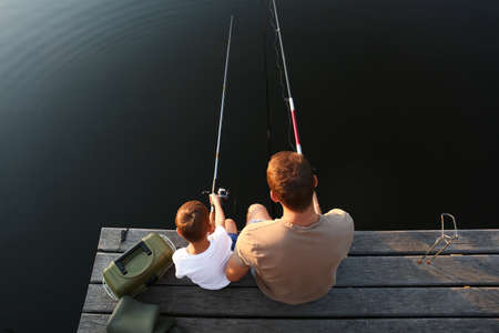 Dad and son fishing together at lake, above view