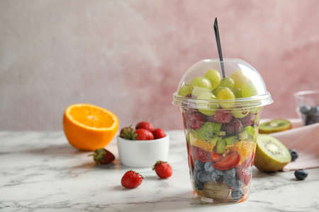 Fresh tasty fruit salad in plastic cup on white marble table. Space for text 版權商用圖片