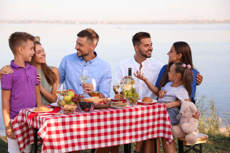 Happy families with little children at picnic table outdoors