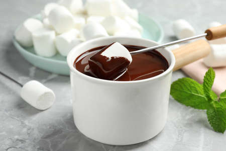 Dipping marshmallow into fondue pot with dark chocolate on marble table, closeup Фото со стока