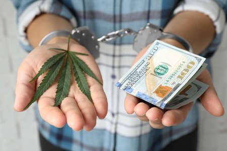 Femme menottée tenant des feuilles de chanvre et des dollars, gros plan