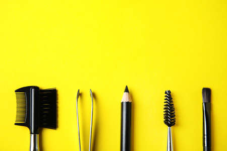 Set of professional eyebrow tools on yellow background, flat lay. Space for text