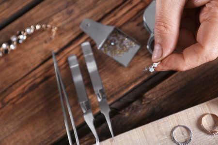 Male jeweler evaluating diamond ring in workshop, closeup view 版權商用圖片