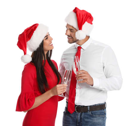 Lovely young couple in Santa hats with glasses of champagne on white background. Christmas celebration