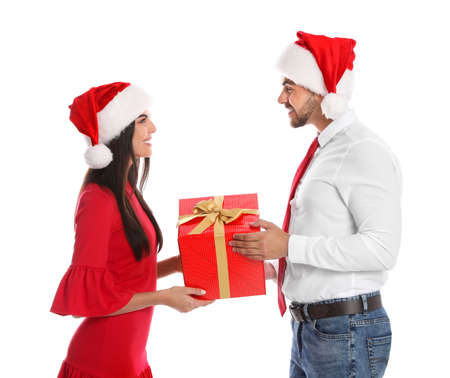 Lovely young couple in Santa hats with gift box on white background. Christmas celebration