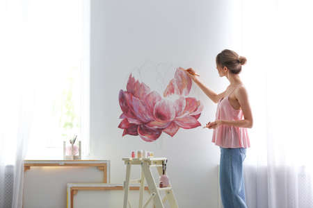 Decorator painting flower on white wall in room. Interior design