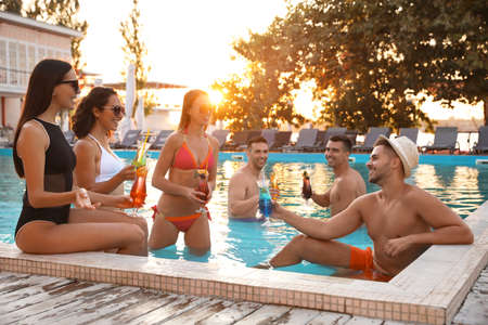 Happy young friends with refreshing cocktails relaxing in swimming pool Reklamní fotografie