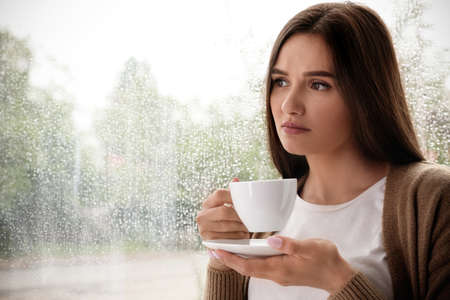 Thoughtful beautiful woman with cup of coffee near window indoors on rainy day