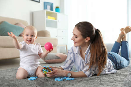 Happy mother playing with little baby on floor indoors Stock Photo