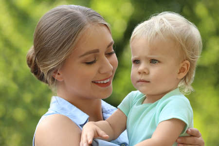 Young mother with her cute child in green park Stock Photo