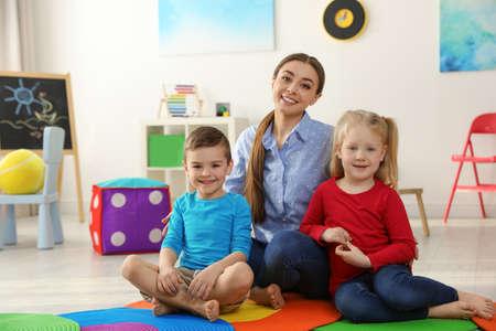 Maestra de jardín de infantes con niños en la sala de juegos. Actividad de interior Foto de archivo