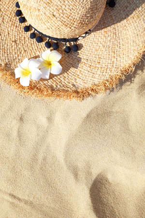 Straw hat on sand, top view with space for text. Beach accessory